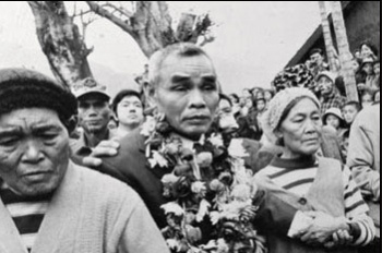 A bewildered-looking Nakamura is garlanded with flowers on his emergence from the jungles of Morotai.