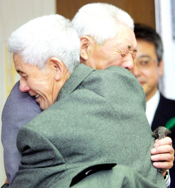 Uwano Ishinosuke (front) hugs his 81-year-old younger brother Sadake Ushitaro as they are reunited for the first time in well over 60 years.